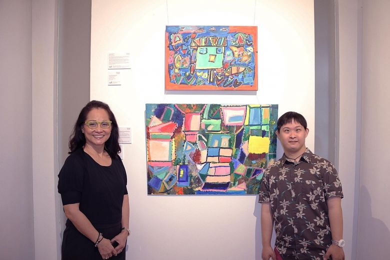 Mr Cavan Chang and his mother Cecilia Lai with his pieces at the Rhythm And Water exhibition. The 30-year-old, who has Down syndrome, enjoys creating abstract art and is keen on the new arts programme.PHOTO: HOSANNA CHANDRASEKRAN